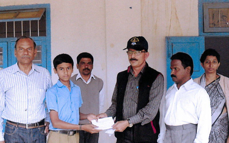 Presenting a cheque to Ammathi High School.