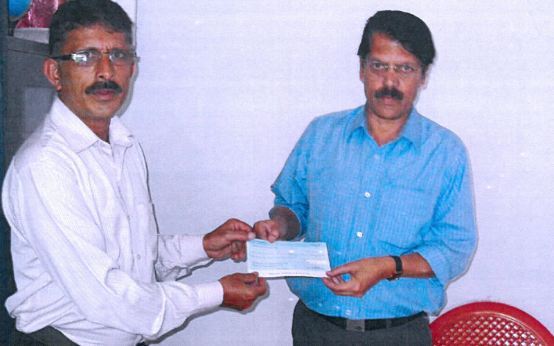 Marchanda Ganesh Ponnappa, Trustee, presenting a cheque to Rotary High School, Bittangala.