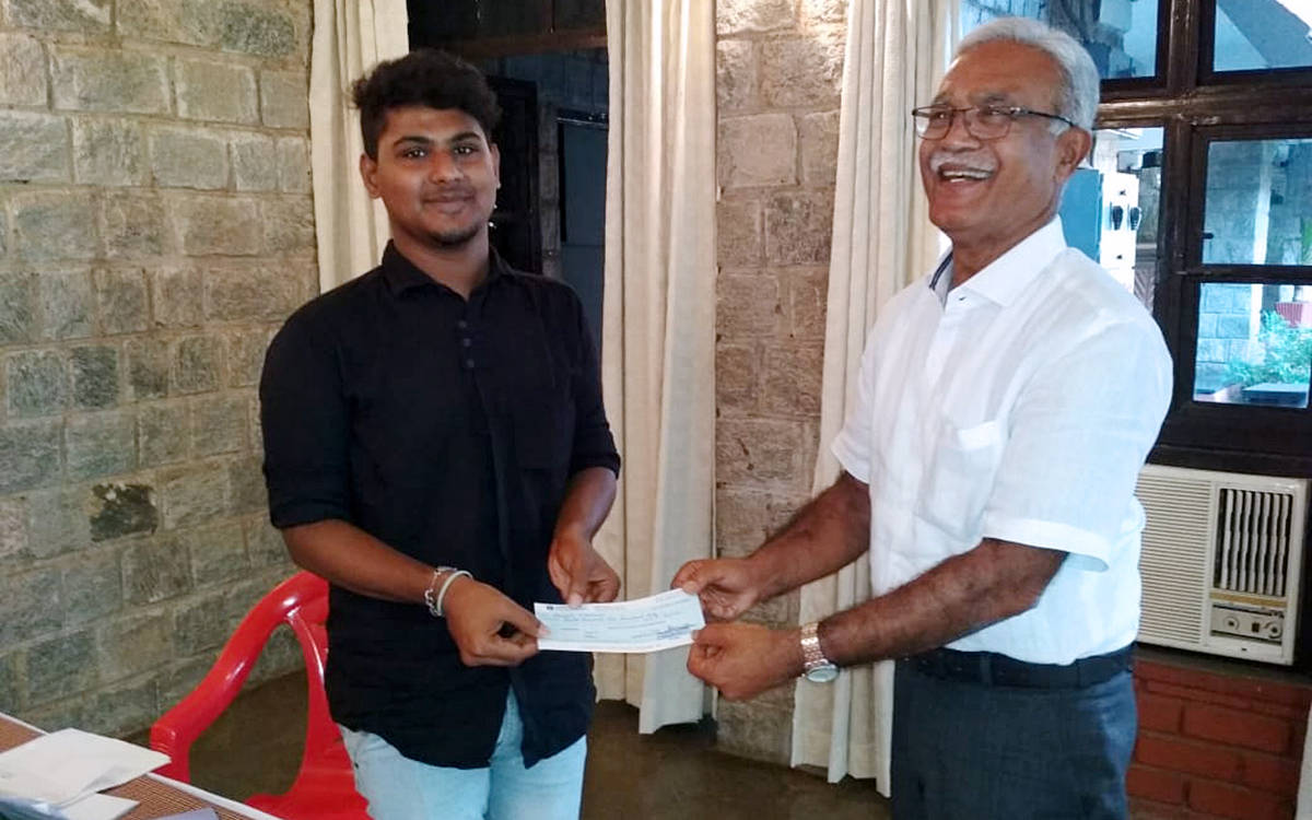 Handing over assistance cheque to beneficiary by President of KESST.